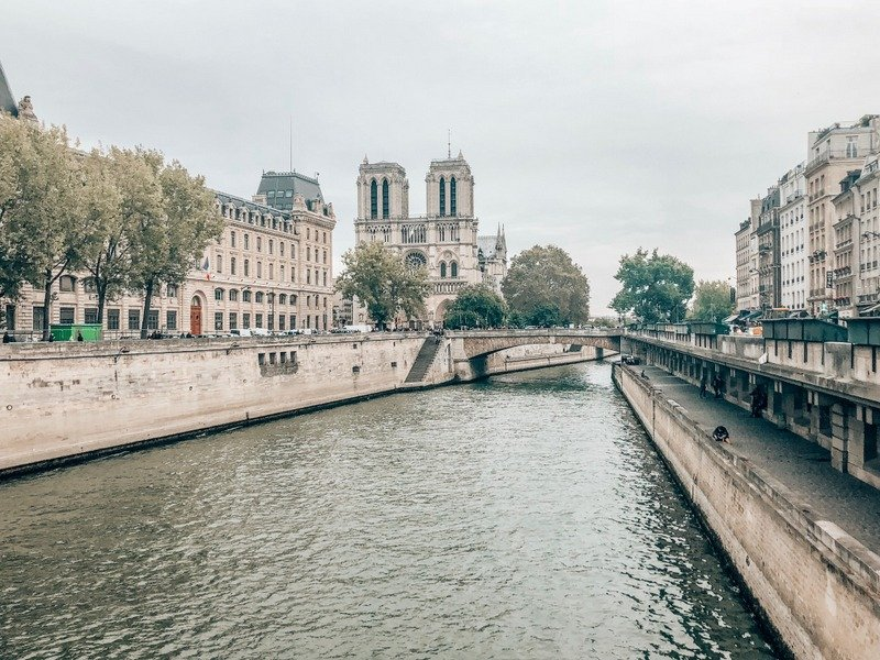 View of the Notre Dame Cathedral by the Seine River Bank